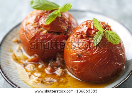 two tomatoes stuffed with rice and cooked in the oven with olive oil - stock photo