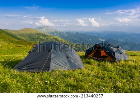 Two tourist tents among green meadow in mountains - stock photo