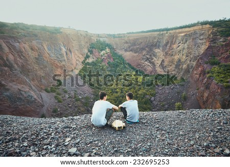 Two tourist young men sitting on rocky cliff and admiring view of abandoned mine  - stock photo