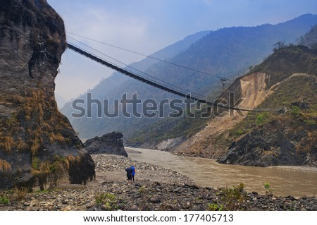 Two tourists with backpacks go below under a suspension bridge on coast of shoaled Marsiandi river in Nepal. - stock photo