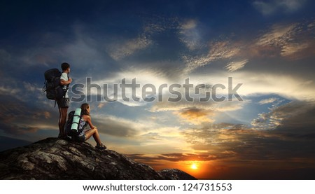 Two tourists with backpacks relaxing on top of a mountain and enjoying sunset view - stock photo