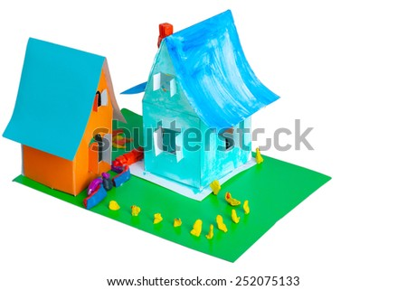 two toy cardboard house on a green lawn on a white background - stock photo