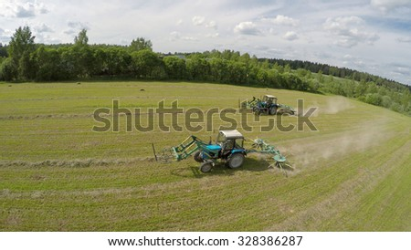 Two tractors work on field near forest at summer sunny day. Aerial view videoframe - stock photo