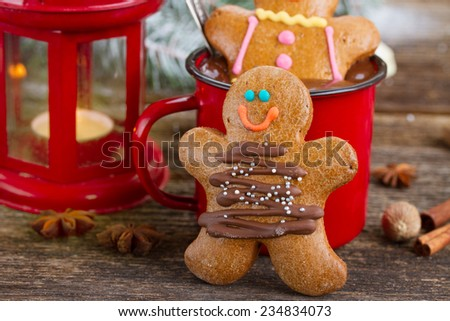 two traditional homemade gingerbread men on wooden table close up  with chocolate in red mug - stock photo