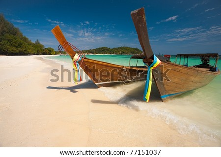 Two traditional longtail boats parked on a white sand beach surrounded by crystal clear turquoise water on the paradise island of Koh Lipe, Ko Lipe, Thailand - stock photo