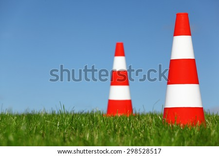 Two traffic cones on a green meadow - stock photo