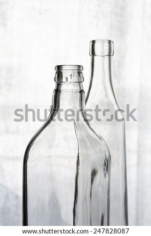 Two transparent crystal bottles against a clear background - stock photo