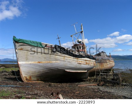 Two trawlers left to rot on a beach on the island of Mull, Scotland - stock photo