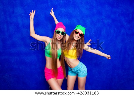 Two trendy women in hats and spectacles dancing on blue background - stock photo