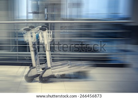 Two trolleys in empty hall of airport, motion blur effect - stock photo