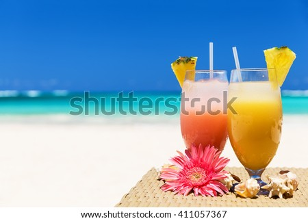 Two tropical fresh juices on white sandy beach - stock photo