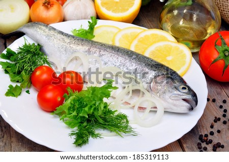 Two trout on a plate with vegetables  - stock photo