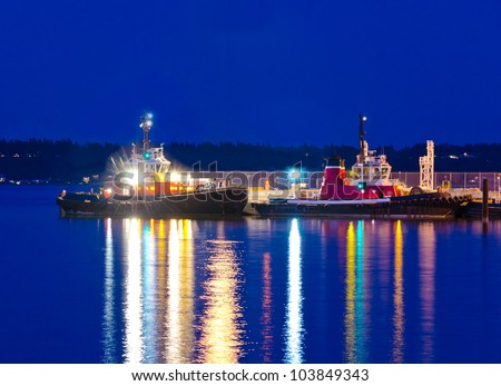 Two tug boats ( tow-boats ) at night time. - stock photo