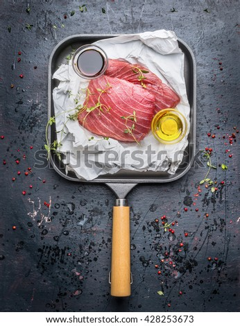 Two tuna steaks in white paper with oil and fresh green seasoning in grill frying pan on dark rustic background, top view. Seafood concept - stock photo
