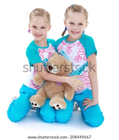 Two twin sisters playing with a teddy bear on a white background.kindergarten, the concept of childhood and joy, teens - stock photo