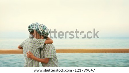 two twins on the quay in the sea hold each other in  brothers friendly embrace in the evening - stock photo