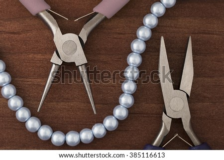 Two types of jewelry making pliers and a string of blue pearls for jewelry making. - stock photo