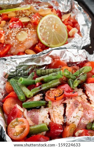 Two uncooked dishes in foil ready for baking - stock photo