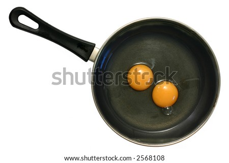 Two uncooked eggs in frying pan on an isolated white background. - stock photo