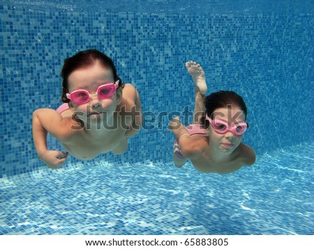 Two underwater kids in swimming pool - stock photo
