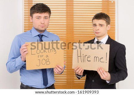 Two unemployed men looking for a job.  Showing plates with sing asking for vacant position  - stock photo