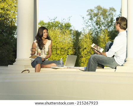 Two university students studying near colonnade, woman beside laptop and textbooks, smiling - stock photo