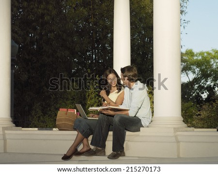 Two university students studying near colonnade, woman with laptop, man holding textbook, smiling - stock photo