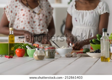 Two unrecognizable african women cooking in kitchen making healthy food salad with vegetables - stock photo