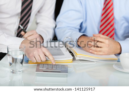 Two unrecognized businessmen working with calculator in the office - stock photo