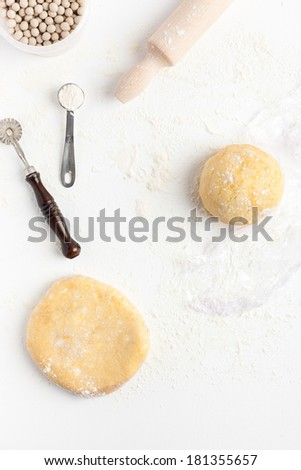 Two unrolled and unbaked shortcrust pastry dough with assorted baking tools: measuring spoon, rolling pin, ceramic baking beans and pastry wheel. Taken on a floured white surface, directly from above. - stock photo
