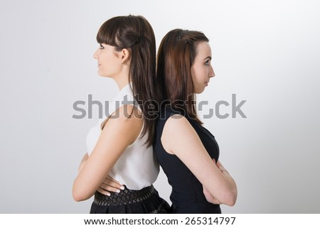 Two upset female friends. teen girls are friends. two girlfriends in school uniform. white background - stock photo