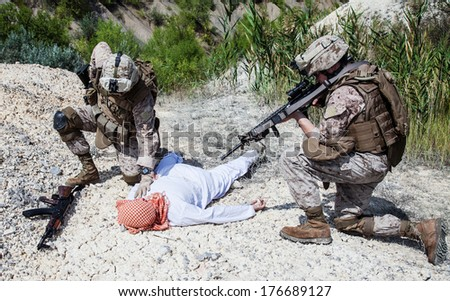 Two US marines making a search of killed muslim warrior - stock photo