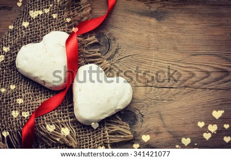 Two Valentine's Day gingerbread heart shape in white glaze on the old table - stock photo