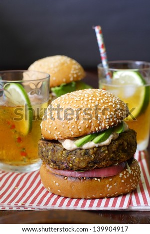 Two vegetarian sweet potato bean burgers with avocado on sesame buns, served with iced tea on a sheet of candy-stripe napkin - stock photo