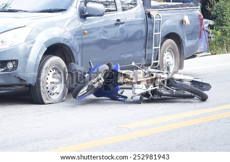Two vehicle head-on accident, caused by one pickup blow out to yield, results in a motorcycle crash. - stock photo