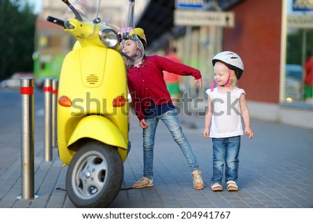 Two very curious little girls and a yellow motorcycle - stock photo