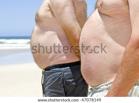 Two very fat men showing their bellies on the beach - stock photo