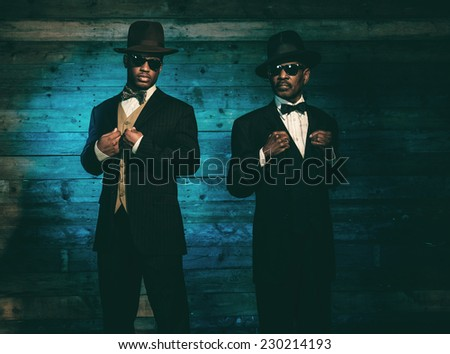 Two vintage african american gangsters in front of old wooden wall. Wearing black sunglasses with suit and hat. - stock photo