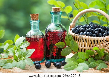 Two vintage bottles of tincture or cosmetic product and basket with blueberries on wooden table. - stock photo