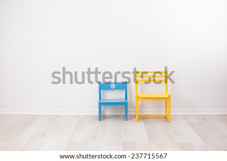 Two vintage child chairs on white wall - stock photo