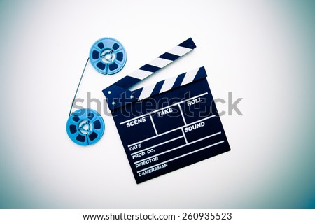 Two vintage 8mm blue reels connected with film and clapper board isolated on white background - stock photo