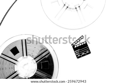 Two vintage 8mm reels connected with film and small clapper board isolated on white background - stock photo