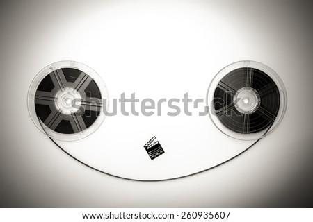 Two vintage 8mm reels horizontally connected with film and a little clapper board sepia black and white - stock photo