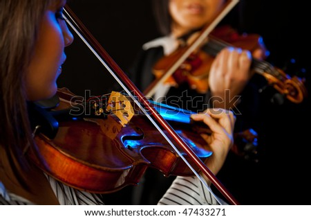 two violinists playing violins on a black background - stock photo