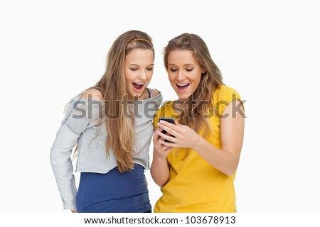 Two voiceless young women looking a smartphone against white background - stock photo