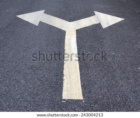 Two way arrow symbol on an asphalt road surface. - stock photo