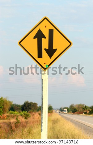 two way arrow traffic sign, road background - stock photo