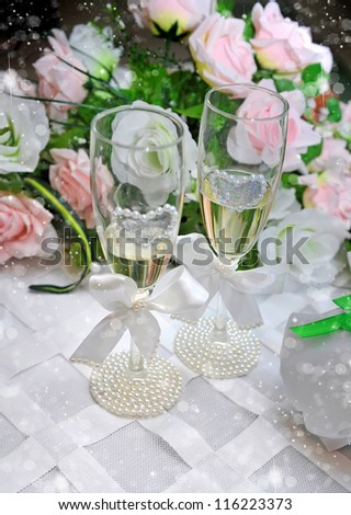 Two wedding glasses of fiancees filled with champagne - stock photo