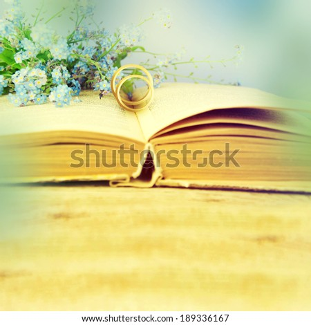 Two wedding rings and blue spring flowers on a bible page. - stock photo