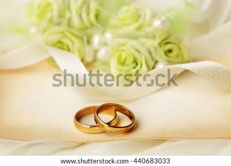 two wedding rings and wedding invitation - stock photo